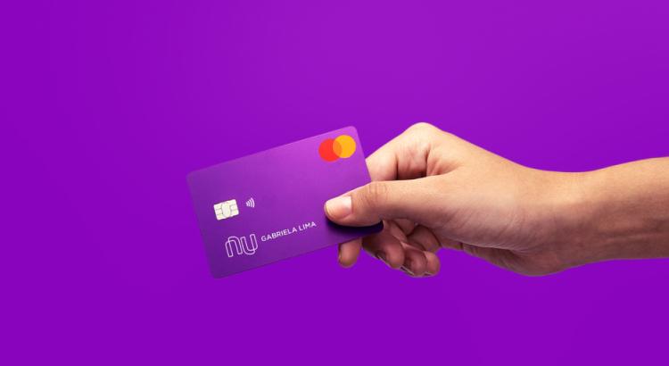 Mão de uma pessoa segurando um cartão em um fundo roxo