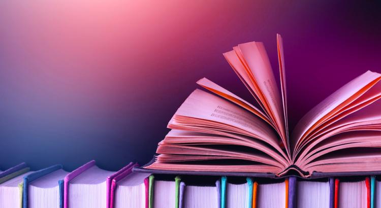Livro aberto com suas folhas voando em cima de outros livros