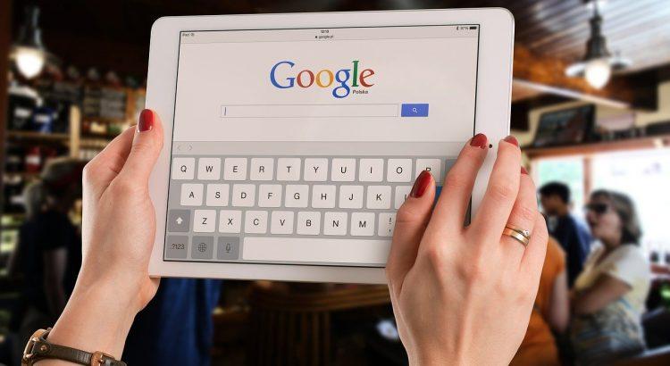 Mão de uma mulher segurando um iPad na página do google