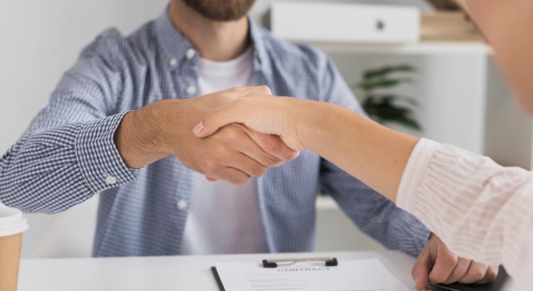 Duas pessoas dando as mãos para fechar um negócio